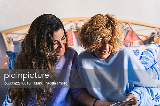 Happy women looking at photograph on bed at home - p300m2276016 by Manu Padilla Photo