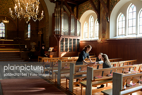 Priests talking on church pews - p352m2121546 by Folio Images