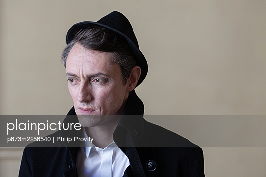 Man in hat looks thoughtful - p873m2258540 by Philip Provily