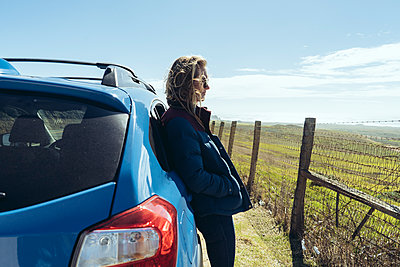 Side view of woman leaning on car against field - p1166m1210058 by Cavan Images