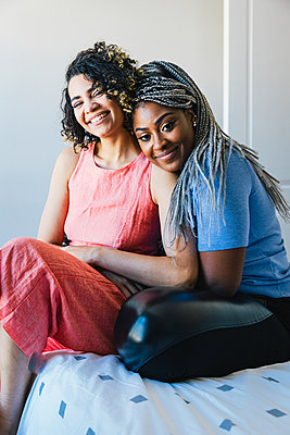 Portrait of happy lesbians sitting on bed at home - p1166m2130586 by Cavan Images