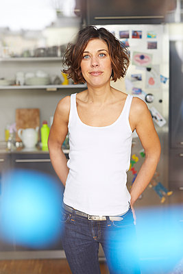 Portrait of mature woman wearing white tank top standing in the kitchen - p300m1587416 von Philipp Nemenz