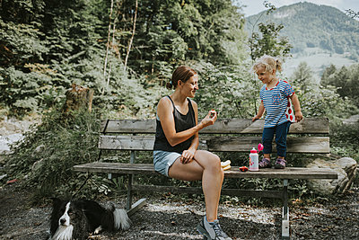 Mother and toddler with dog on a bench in forest - p300m2029234 by Frederik Franz