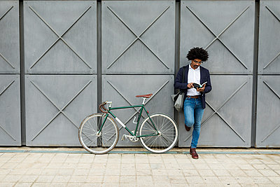 Businessman with bicycle leaning against a wall reading book - p300m2104420 von Valentina Barreto