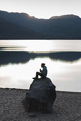 Man sitting on rock at lake during sunset - p300m2282003 by Josu Acosta
