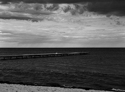 Long wooden dock stretching out in the ocean - p3485170 by Patrik Thalén