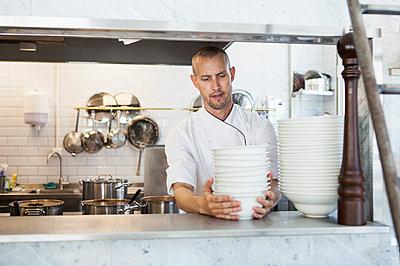 Chef arranging bowls in restaurant kitchen - p426m977414f by Astrakan