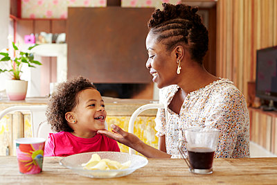 Mother and daughter talking at breakfast table - p555m1454087 by Granger Wootz