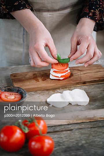 Woman's hands preparing Caprese Salad - p300m2012399 von Alberto Bogo