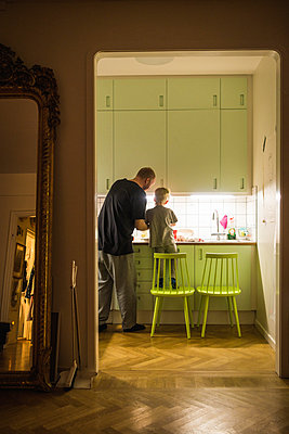 Father and son in the kitchen - p1418m1571502 by Jan Håkan Dahlström