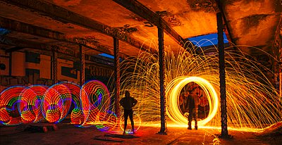 Man and woman creating multi-color and golden spark light trails in derelict building - p429m1103290 by Pete Saloutos