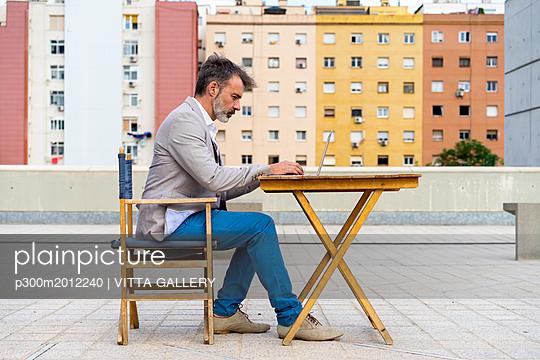 Businessman sitting on roof terrace working on laptop - p300m2012240 von VITTA GALLERY