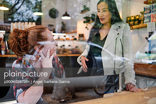 Pregnant woman with hand on stomach talking with female friend in cafe - p300m2287281 by Angel Santana Garcia