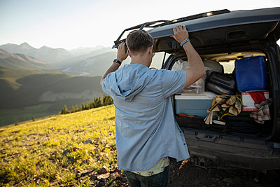 Man preparing for camping at back of SUV, Alberta, Canada - p1192m2016595 by Hero Images