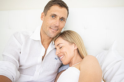 Happy couple sitting on bed, portrait - p1640m2259613 by Holly & John