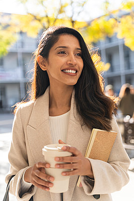 Smiling young woman with book and takeaway coffee in the city looking around - p300m2166191 by VITTA GALLERY