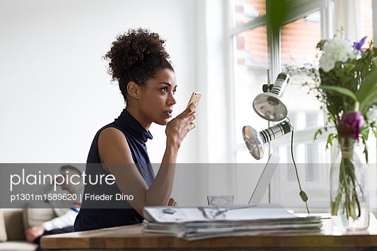 Junge Geschäftsfrau sitzt am Arbeitsplatz und gibt eine Sprachnachricht in ihr Handy ein  - p1301m1589620 von Delia Baum