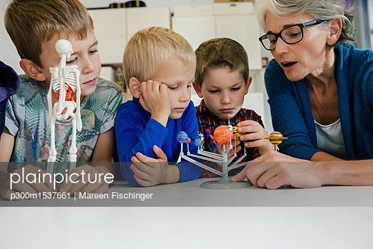 Pre-school teacher explaining solar system model to boys in kindergarten - p300m1537661 by Mareen Fischinger