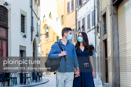Tourist couple with protective face mask holding hands while walking on city street - p300m2287319 by Emma Innocenti