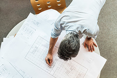 Architect working on ground plan in office - p300m1189640 by Tom Chance