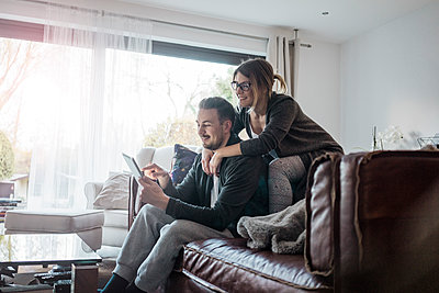 Smiling couple sittng on couch at home using tablet - p300m1535980 by Robijn Page