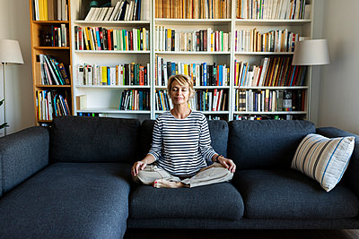 Mature woman practicing yoga on couch at home - p300m2144947 by Valentina Barreto