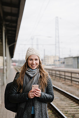 Portrait of smiling young woman with backpack and smartphone standing on platform - p300m2154575 by Hernandez and Sorokina