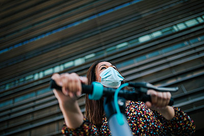 Mature woman in protective face mask with electric scooter against building during coronavirus crisis - p300m2225763 by LUPE RODRIGUEZ
