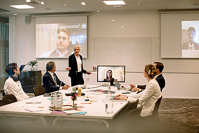 Mature businesswoman giving presentation to colleagues in board room during global conference meeting at office - p426m2187218 by Maskot
