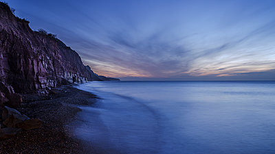 Receding wave beneath cliffs at the picturesque seaside town of Sidmouth, Devon, England, United Kingdom - p871m2113742 by Baxter Bradford