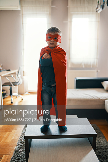 Little boy dressed up as a superhero standing on coffee table at home - p300m1581727 von Zeljko Dangubic
