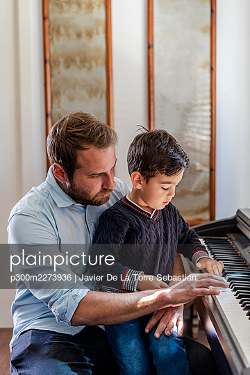Father teaching piano to son sitting on lap at home - p300m2273936 by Javier De La Torre Sebastian