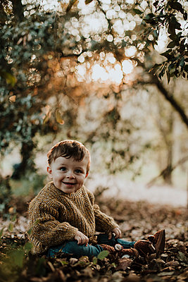 Cheerful toddler sitting amidst dry autumn leaves while looking away in forest - p300m2251674 by Gala Martínez López