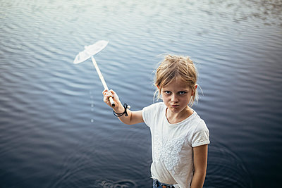 Portrait of girl with fishing net against lake - p426m2212171 by Maskot