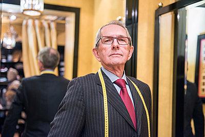Senior tailor in tailors shop, portrait - p429m2004155 by G. Mazzarini