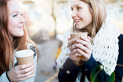 Women having coffee together outdoors - p924m807248f by Sydney Bourne