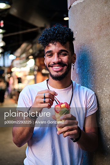 Smiling young man having fruit salad while standing by wall - p300m2293225 by Alvaro Gonzalez