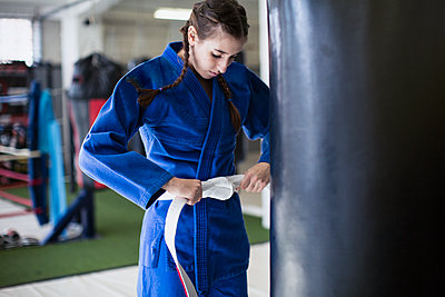 Young woman tightening judo belt at punching bag in gym - p1023m1506472 by Sam Edwards
