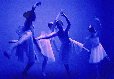 Ballerinas dancing on stage bathed in blue light - p1072m829014 by George Robinson