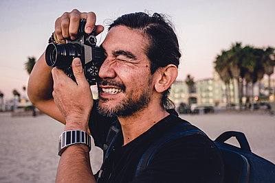 Close-up of backpacker photographing with camera at beach - p1166m1556351 by Cavan Images