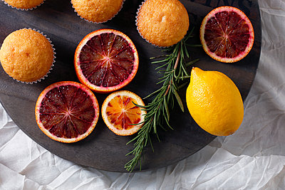 High angle view of fairy cakes with rosemary and citrus fruits on cutting board - p1166m1561226 by Cavan Images