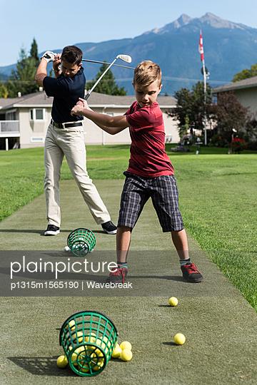 plainpicture - plainpicture p1315m1565190 - Father and son hitting golf... - plainpicture/Wavebreak