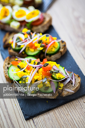 Vegetarian breakfast with bread, eggs and cucumber slices on slate - p300m1587154 von Giorgio Fochesato