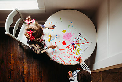 Young girl and boy painting art on small white table inside - p1166m2124344 by Cavan Images
