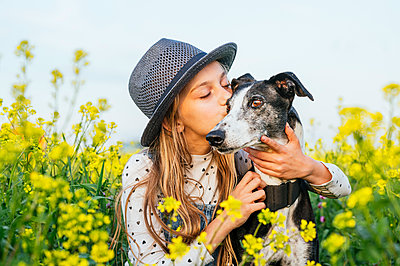 Girl with eyes closed kissing dog while at agricultural field - p300m2282183 by Jose Luis CARRASCOSA