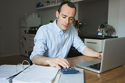 Serious man working over documents with laptop and calculator at home - p301m1148386 by Halfdark