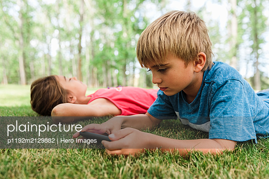 Boy lying on grass using smartphone - p1192m2129882 by Hero Images