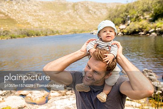 Vater und Baby am Seeufer - p1355m1574029 von Tomasrodriguez