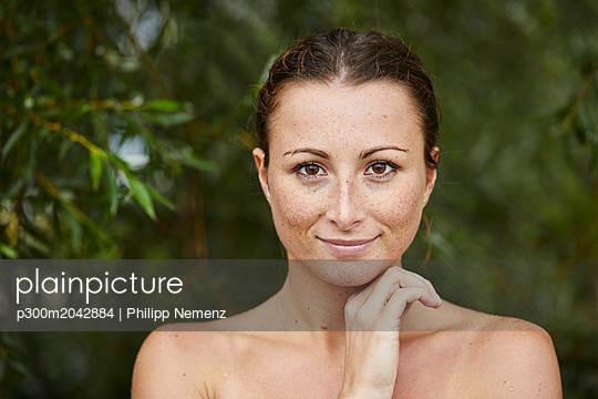Portrait of freckled young woman in nature - p300m2042884 von Philipp Nemenz