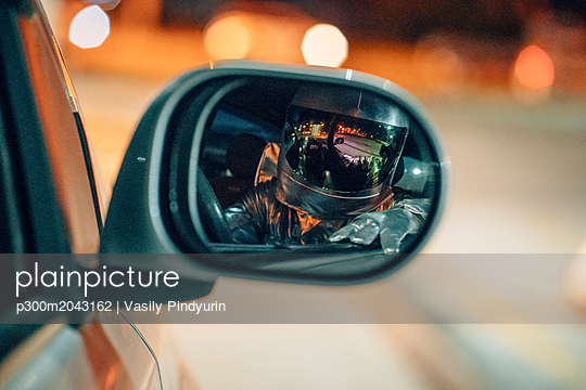 Reflection of spaceman in wing mirror of a car at night - p300m2043162 by Vasily Pindyurin